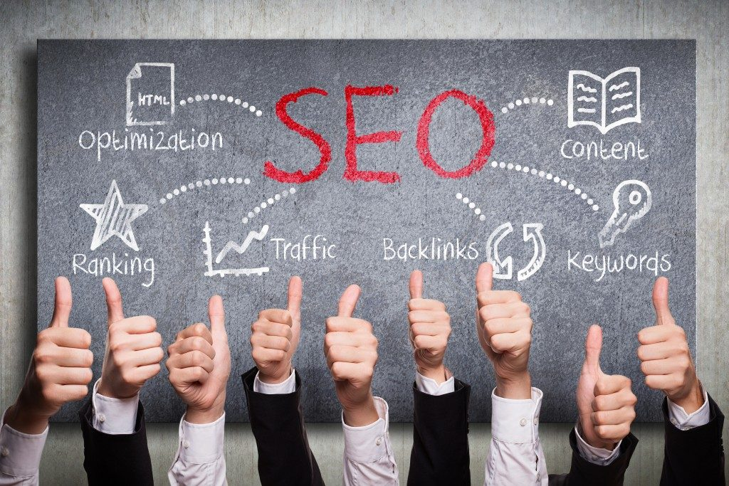 thumbs of people up above the written SEO