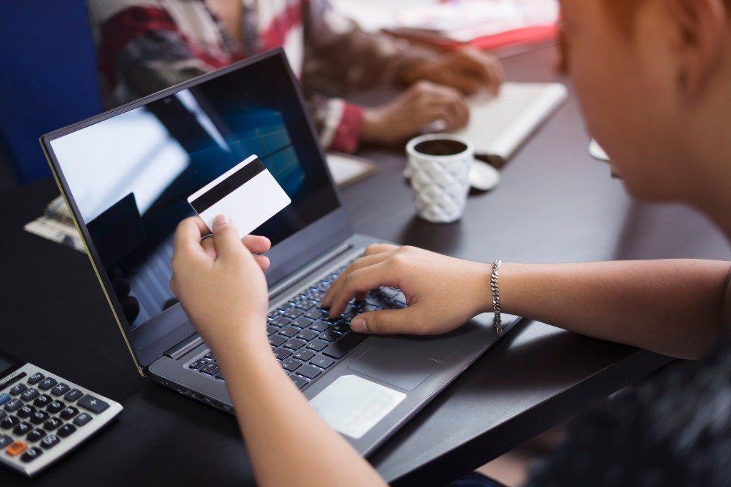 Man using his laptop while looking at his credit card