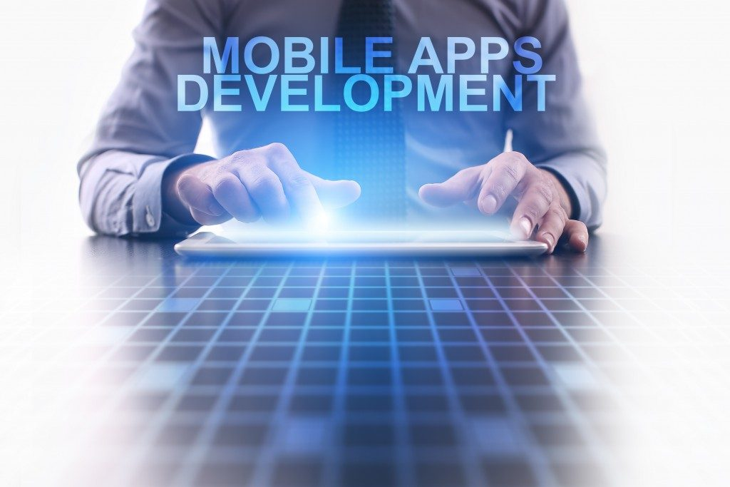 Businessman using tablet pc and select Mobile apps development.